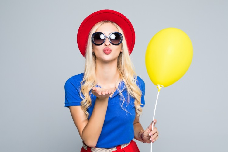 Pretty-young-woman-in-sunglasses-with-air-balloon-sends-an-air-kiss-over-gray-background-845194082_2