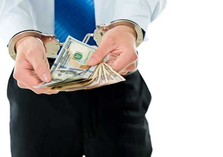 Businessman-hands-in-handcuffs-holding-US-dollars-543599726_6882x4820.jpeg