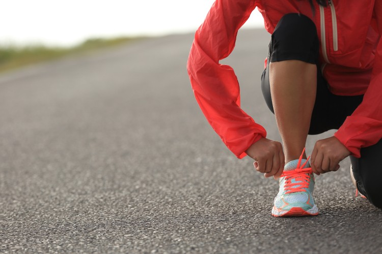 young-woman-runner-tying-shoelace-on-country-road-576927574_5760x3840.jpeg