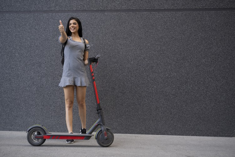 cheerful-young-woman-next-to-electric-scooter-thumbs-up-1163337952_2125x1416.jpeg