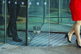 Busnessman-And-Businesswoman-Walking-Through-Revolving-Door-482802851_1800x1200.jpeg
